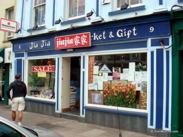 """Jia Jia Market, Cornmarket St. - A view of a blue building with various flyers sitting in the window next to a mural of flowers. In the background, there is a stack of bags of rice and above the door is a sign that reads """"Jia Jia Market and Gifts"""""""